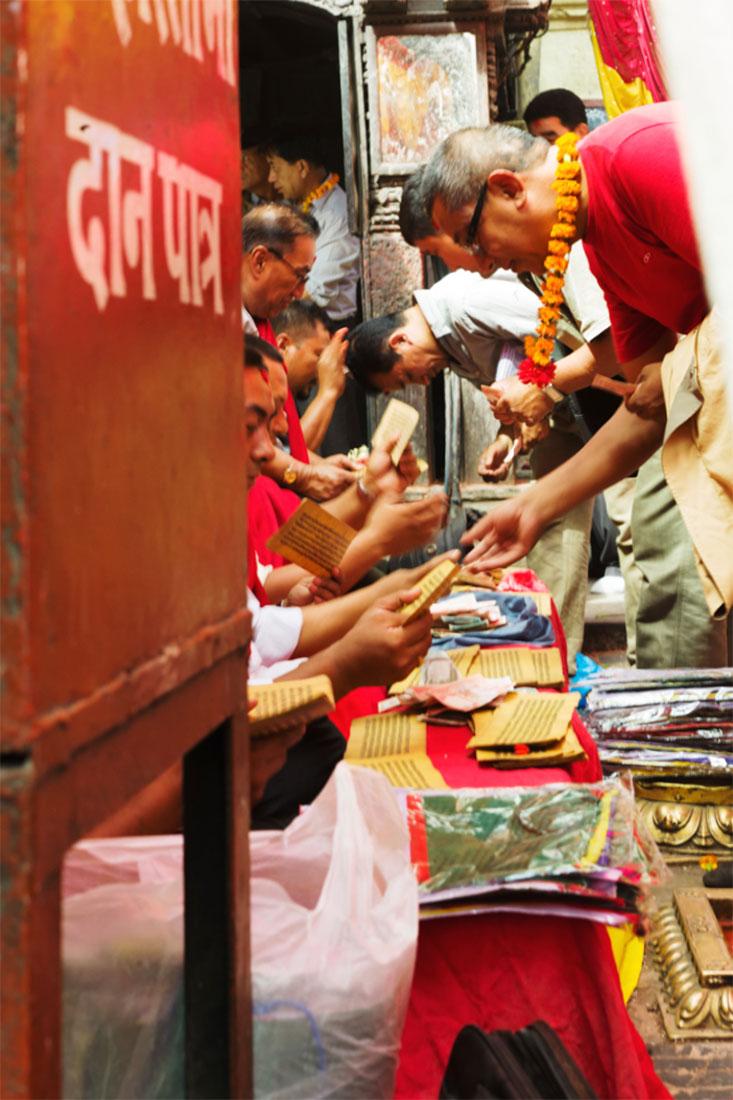 Monges recebem oferendas das pessoas num templo budista da cidade de Kathmandu.