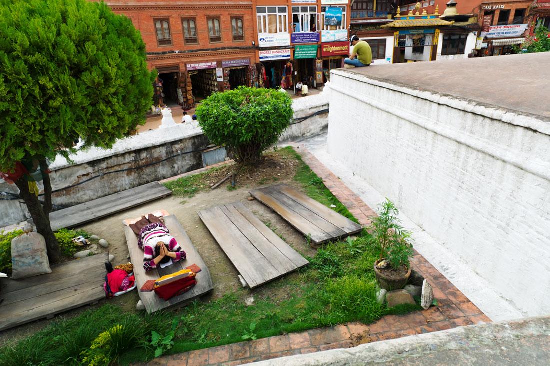 Mulher reza em pequeno jardim junto a um dos muros laterais da Boudhanath Stupa em Kkathmandu.