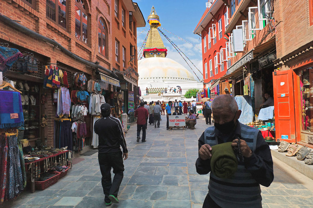 Olhos de Buda no topo da Boudhanath Stupa, desde uma rua com lojas de artesanato.