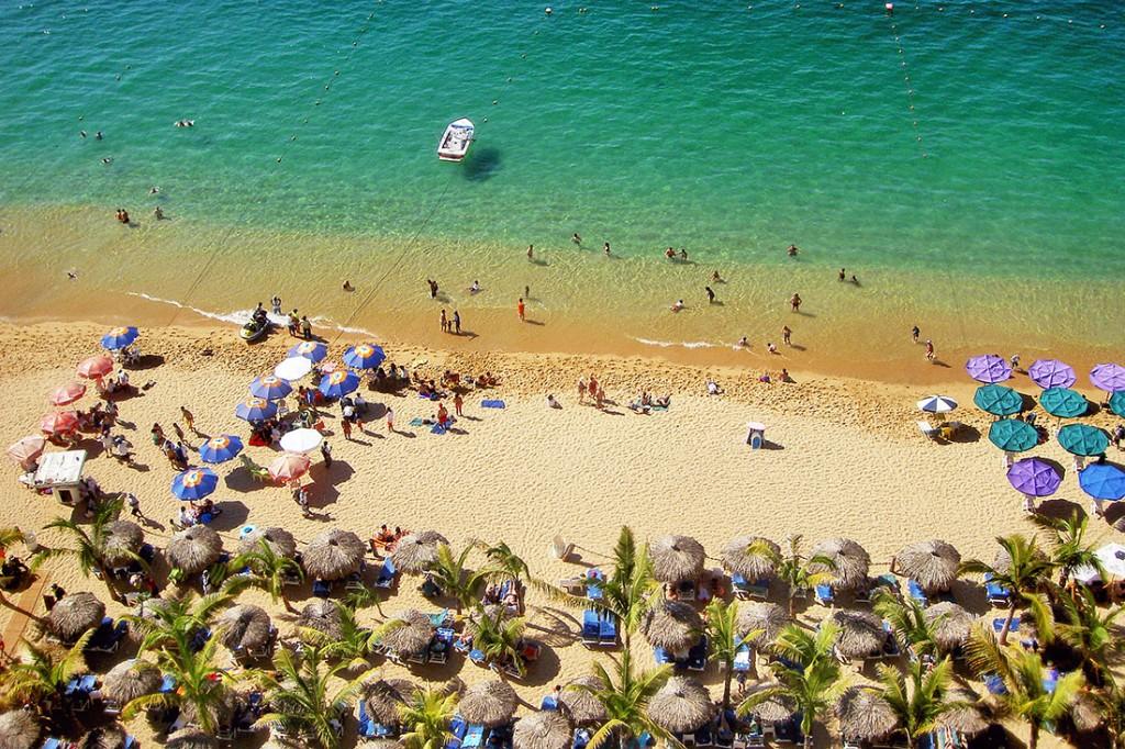 Praia em Acapulco cheia de chapéus-de-sol e águas verde-esmeralda.