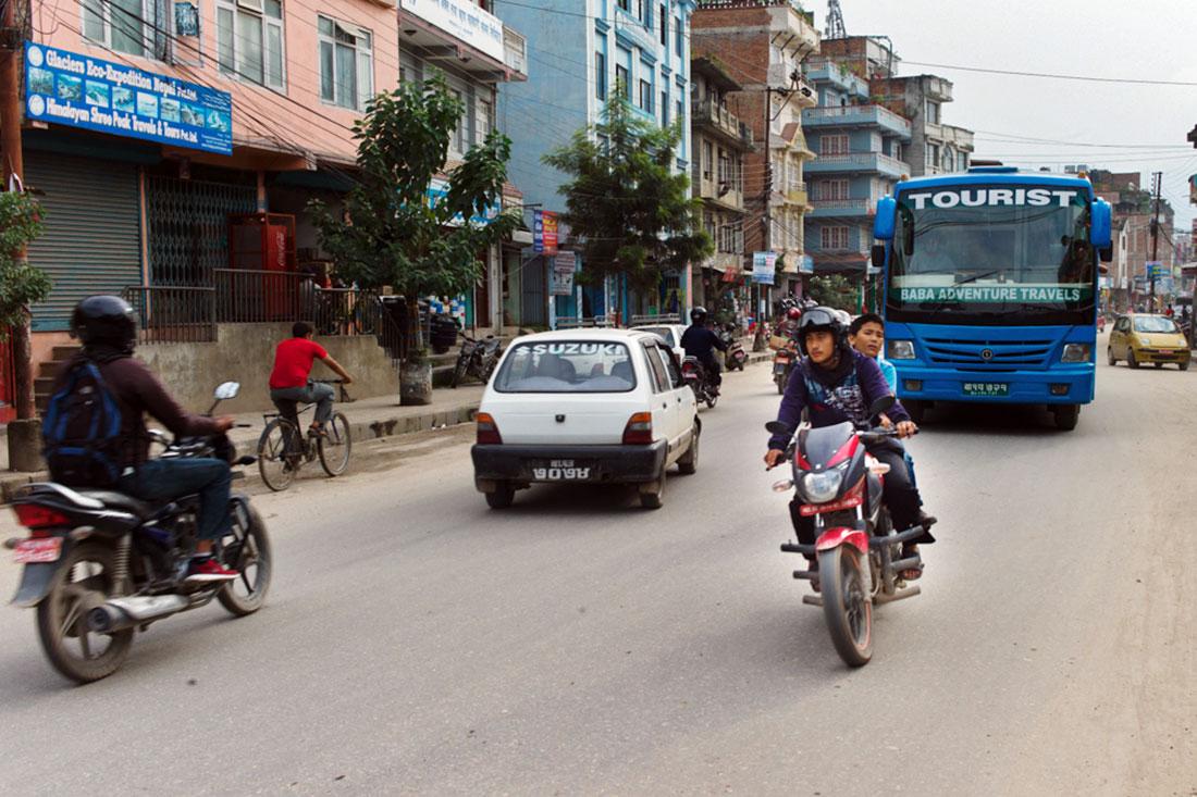 Rapazes aceleram numa moto a grande velocidade por entre o transito de Kathmandu.