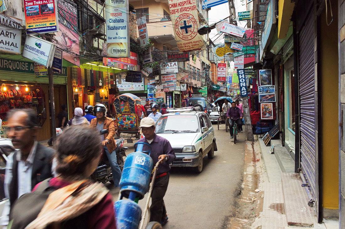 Grande confusão de gente, veículos e placards em prédios, numa rua do bairro de Thamel.