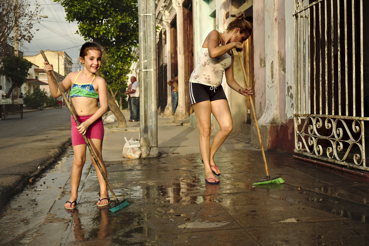 Mãe e filha em limpezas, num passeio de cimento molhado, na cidade cubana de Cienfuegos.
