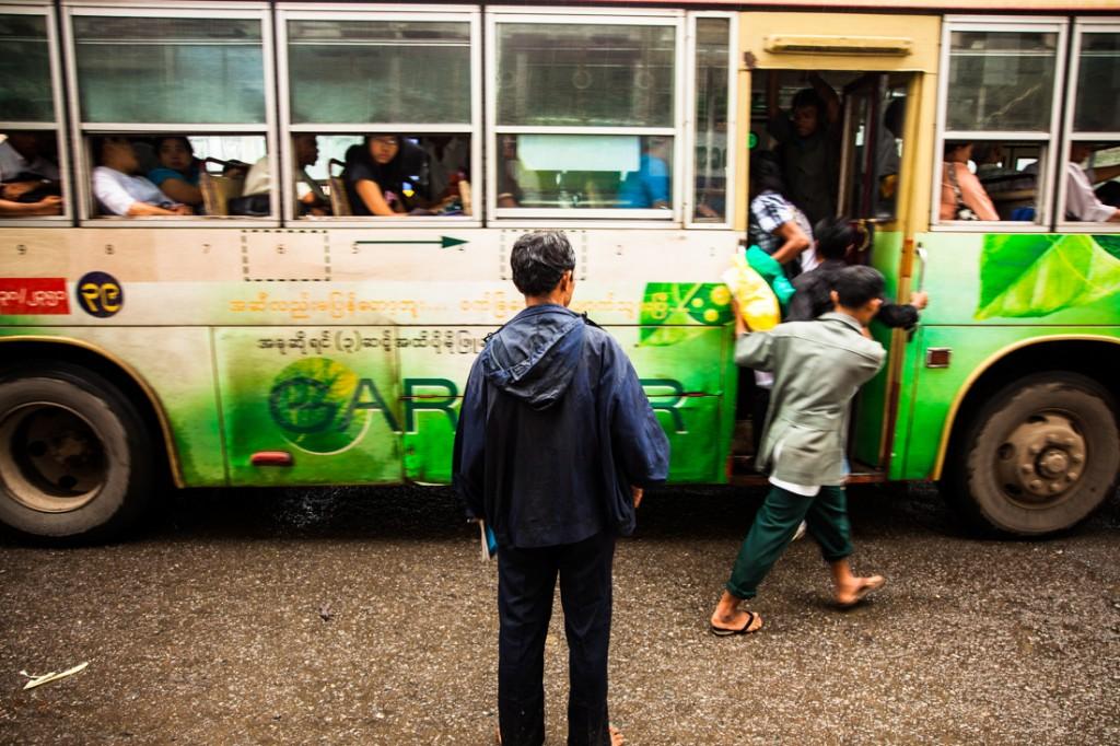 Ajudante e cobrador de autocarro em Yangon.