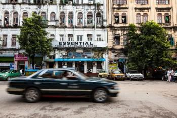 Carro a passar na baixa de Yangon, zona ainda muito marcada pela traça colonial dos edifícios.