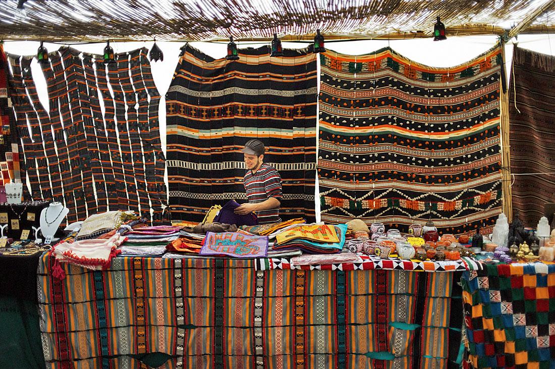Vendedor na sua banca de produtos árabes e tapeçarias à espera de clientes.