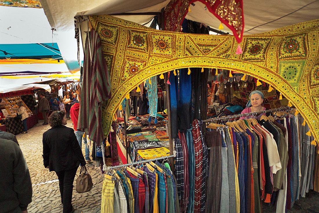 Pessoas a observar roupas numa banca no Festival Islâmico de Mértola.