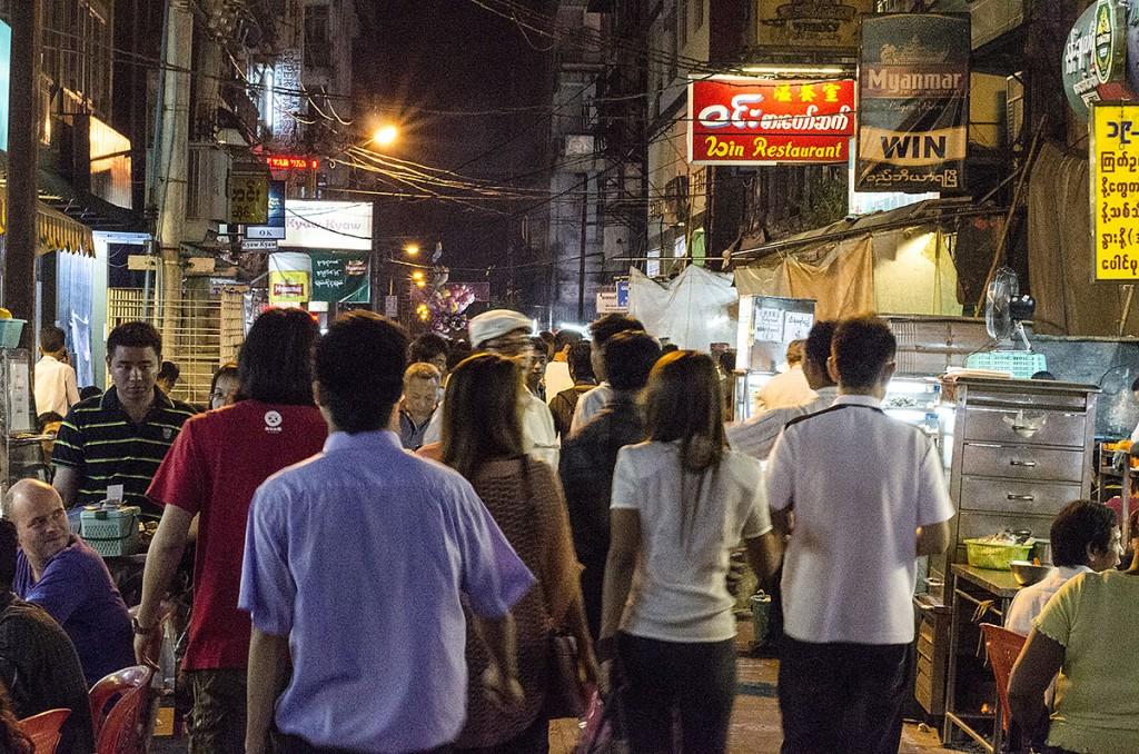 Grande movimento de pessoas a circular numa rua de Yangon, já durante a noite.