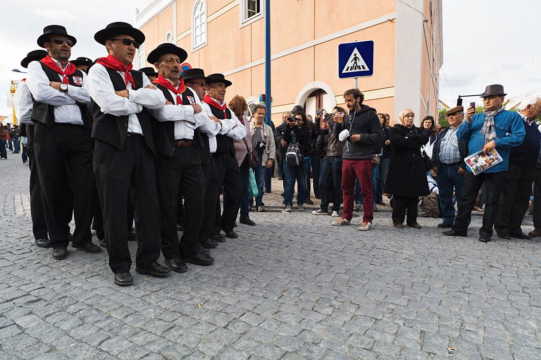 Grupo de cantares alentejanos, fardados com roupa típica e lenço vermelho, a desfilar nas ruas de Mértola, durante o festival islâmico.