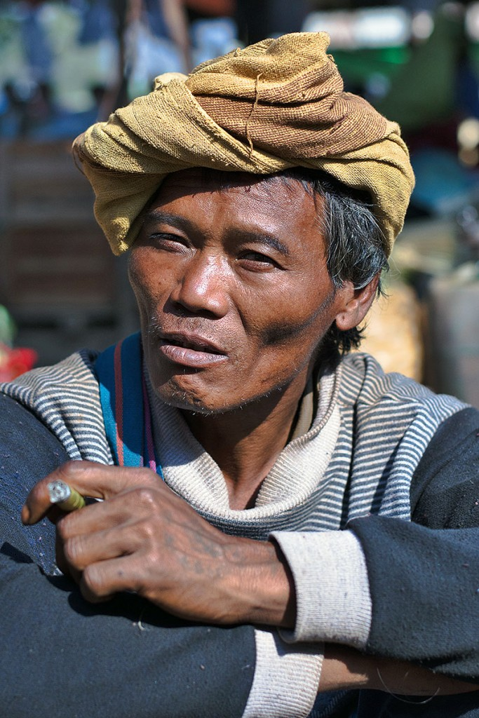 Homem de etnia Intha a fumar junto ao lago Inle.