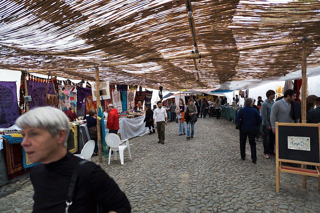 Pessoas no largo junto à igreja antiga de Mértola, agora parte do souk improvisado para o festival islâmico.