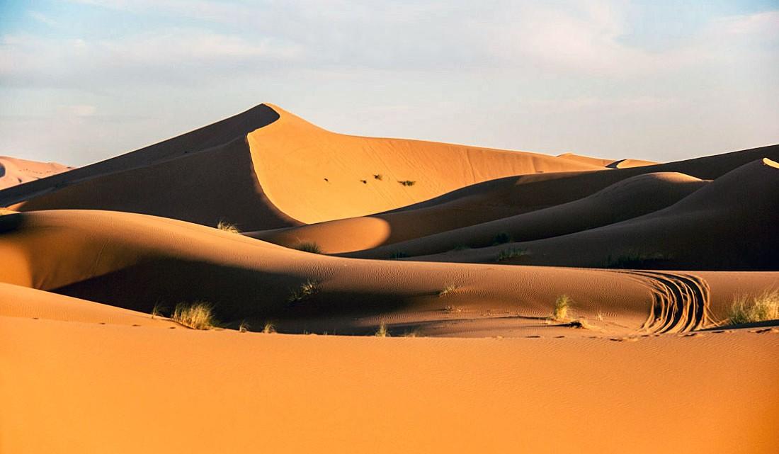 Nuances cromáticas e luz laranja nas dunas de Erg Chebbi.