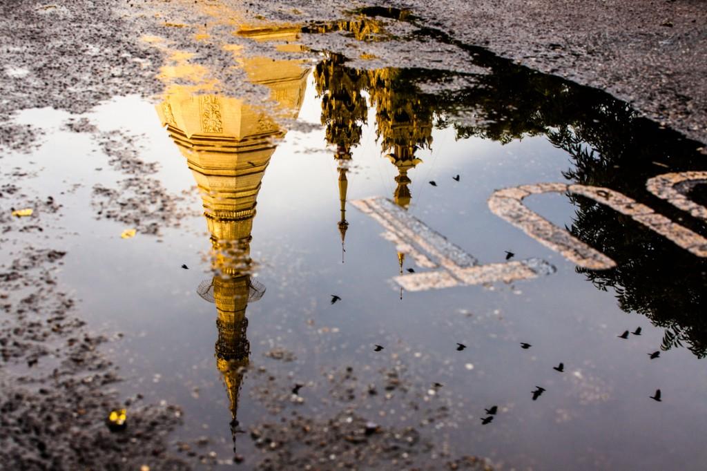 Pagode Sule Paya reflectido numa poça de água numa estrada de Yangon.