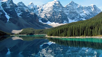 Montanhas com neve reflectidas nas águas de um lado do Parque Nacional Waterton, parte das Rocky Mountains no Canadá.