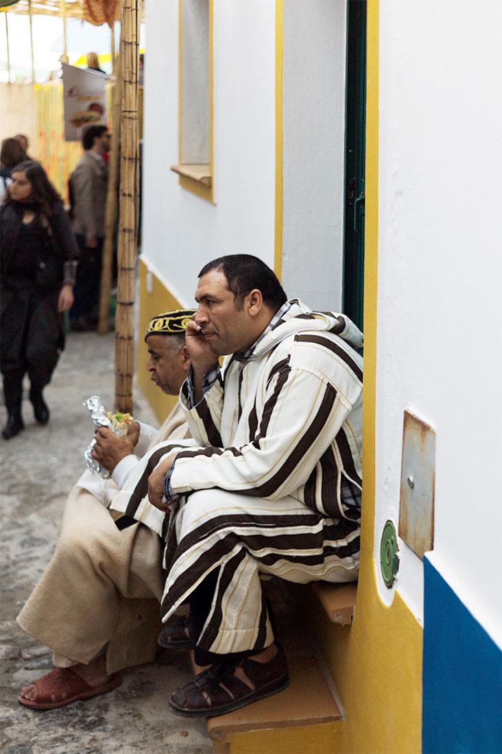 Marroquinos sentados na soleira de uma porta em Mértola durante o almoço.