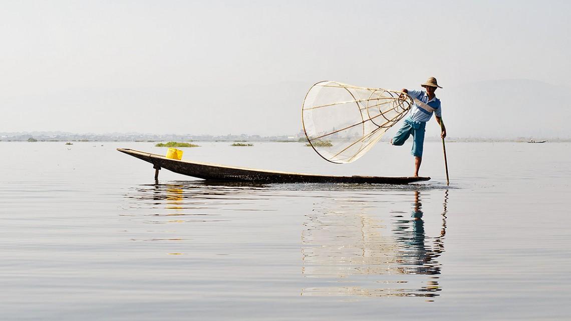 Pescador sobre a sua canoa a pescar com artes de pesca tradicionais do lago Inle, em Myanmar.
