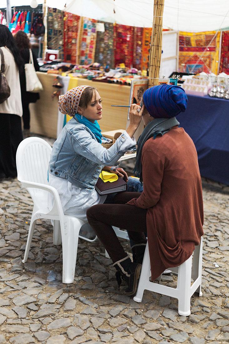 Mulher a ser pintada na face durante o Festival Islâmico de Mértola.
