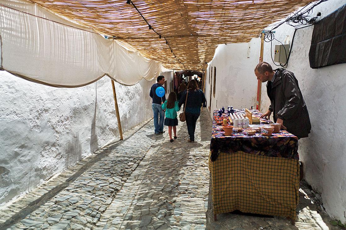 Rua típica de Mértola, com paredes brancas e pavimento empedrado, durante o festival islâmico.