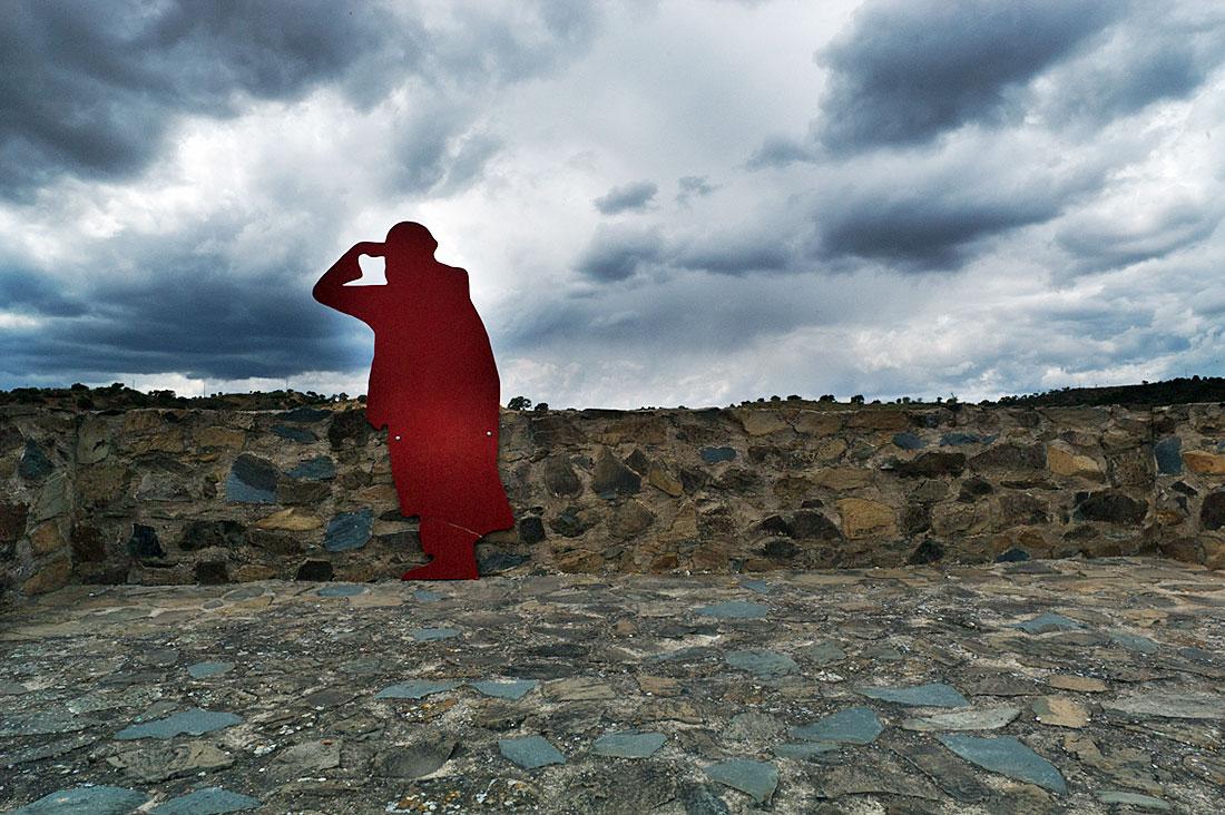Silhueta vermelha de mouro junto à muralha de Mértola com céu carregado de nuvens.