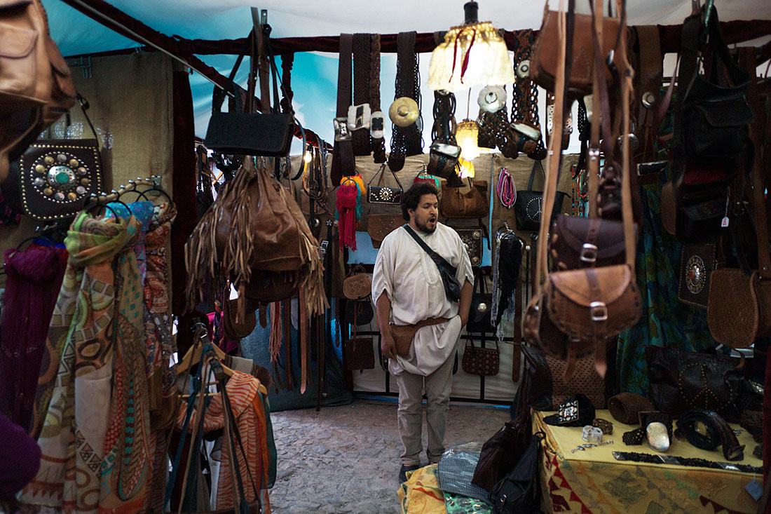 Tenda com vendedor marroquino e muitos produtos de marroquinaria durante o Festival Islâmico de Mértola.