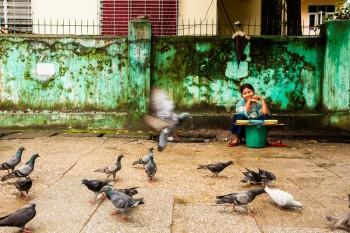 Vendedora de comida para pombos nas ruas de Yangon.