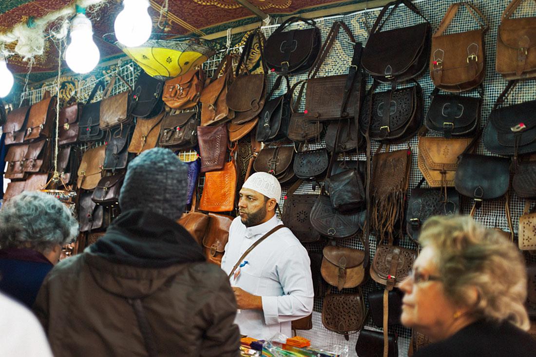 Clientes interessados na marroquinaria de um vendedor marroquino no Festival Islâmico de Mértola.