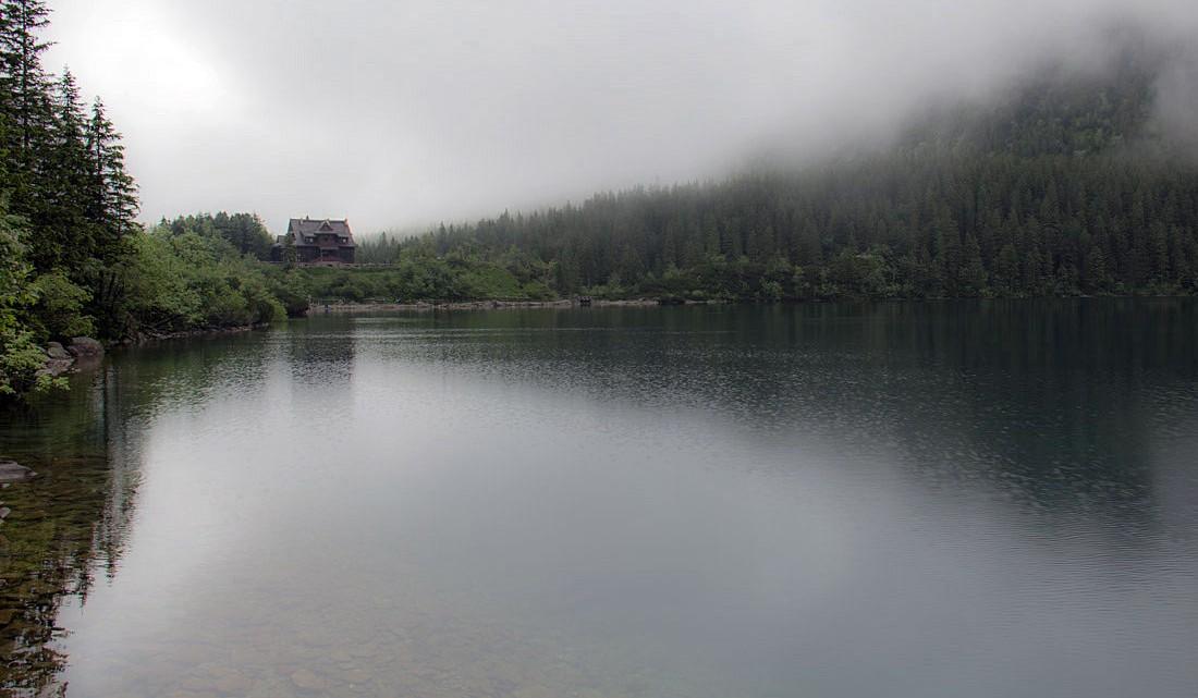 Espelho de água do lago Morskie Oko, envolto em nevoeiro, com casa abrigo ao fundo.