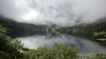 Lago Morskie Oko envolvido por vegetação luxuriante e um denso nevoeiro.