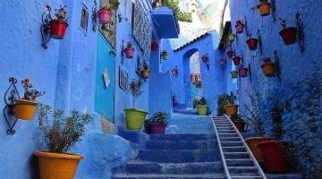 Rua acentuada cheia de vasos nas paredes azuis da medina de Chefchaouen.