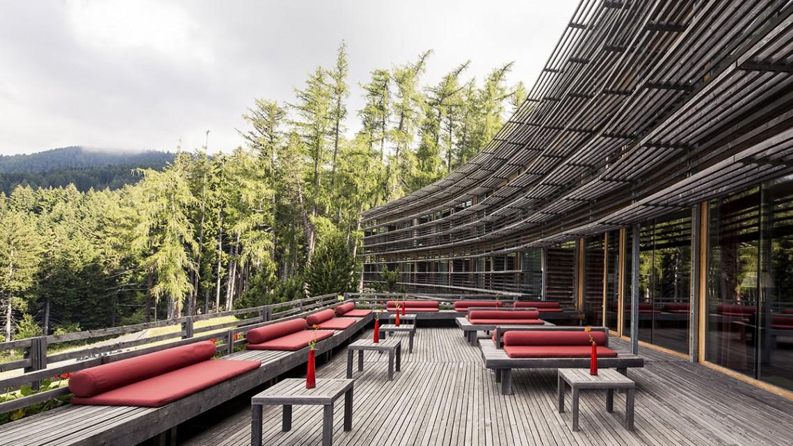Bancos e mesas no terraço de madeira do Vigilius Mountain Resort virado para a montanha.