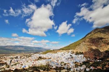 Cidade de Chefchaouen no sopé da montanha debaixo de um céu azul.