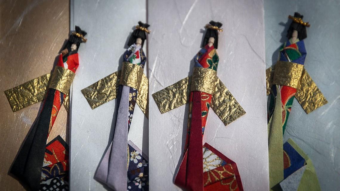 Bonecas japonesas sobre papéis de várias tonalidades.