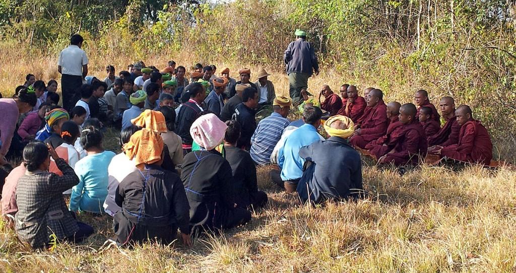Aldeões e grupo de monges budistas na celebração dos rituais de um funeral numa aldeia de Myanmar.