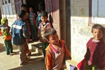Crianças no recreio junto à entrada de uma escola nas montanhas de Shan, em Myanmar.