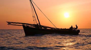 Dhow, o barco com velas em forma triangular típico do Oceano Indico, no caso junto à ilha de Zanzibar ao pôr-do-sol.