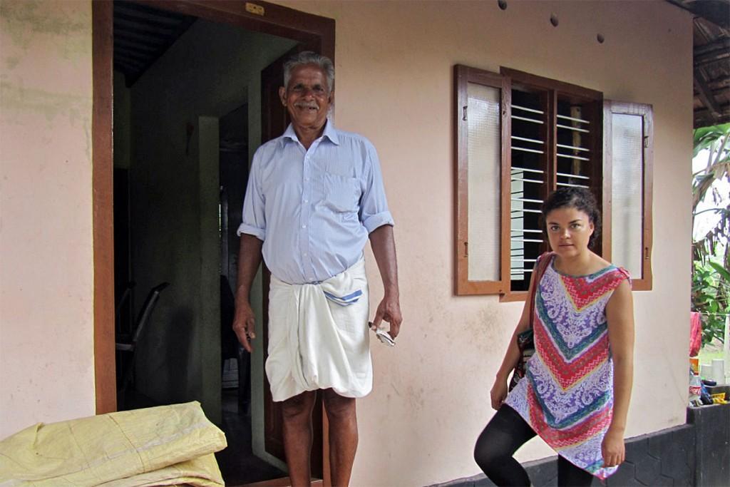 Homem indiano, vestido com um lungi, à entrada da sua casa em Alappuzha.