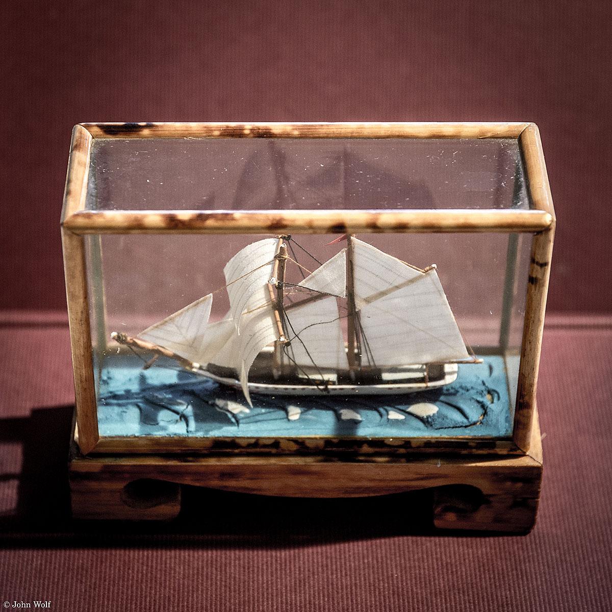 Maquete de barco dentro de uma vitrina de vidro e madeira.