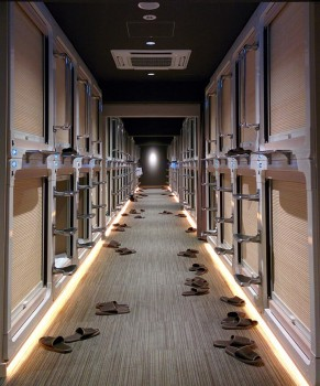 Corredor de hotel cápsula com chinelos junto à entrada de cada compartimento.