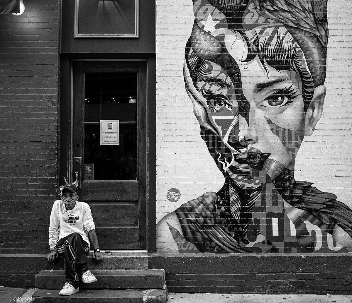 Homem sentado numas escadas, junto a um mural, em Nova Iorque.