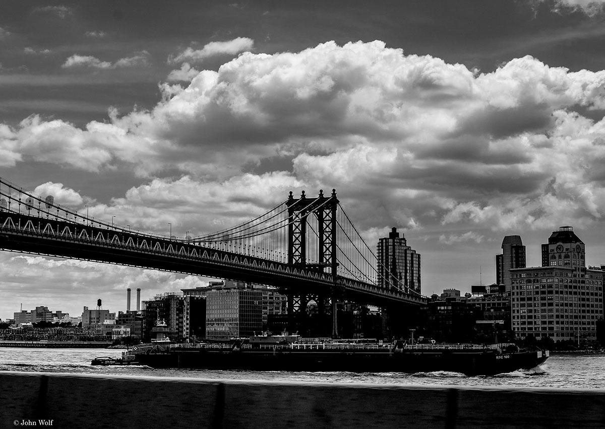 Ponte de Brooklyn, sobre o rio East e sob um céu carregado de nuvens.