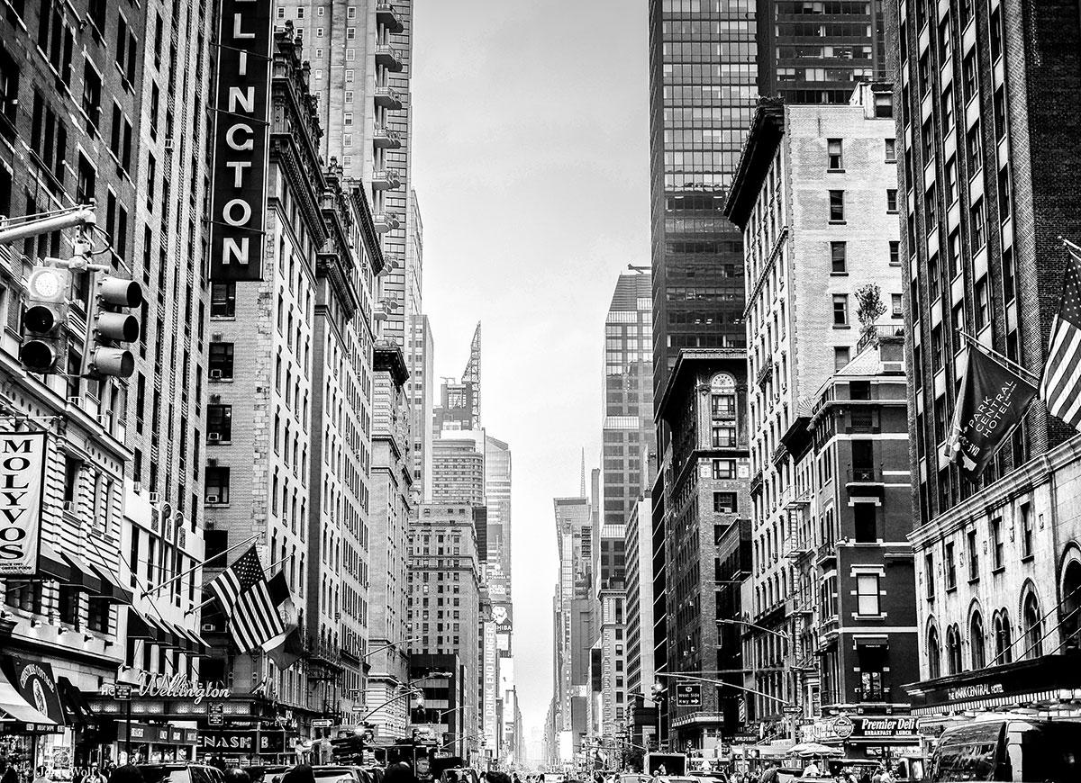5a avenida em Nova Iorque, ladeada por prédios altos, bandeiras e muitas lojas.