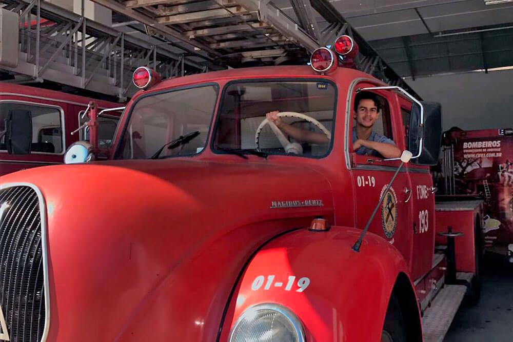 Átila Muniz dentro de camião de bombeiros vermelho.