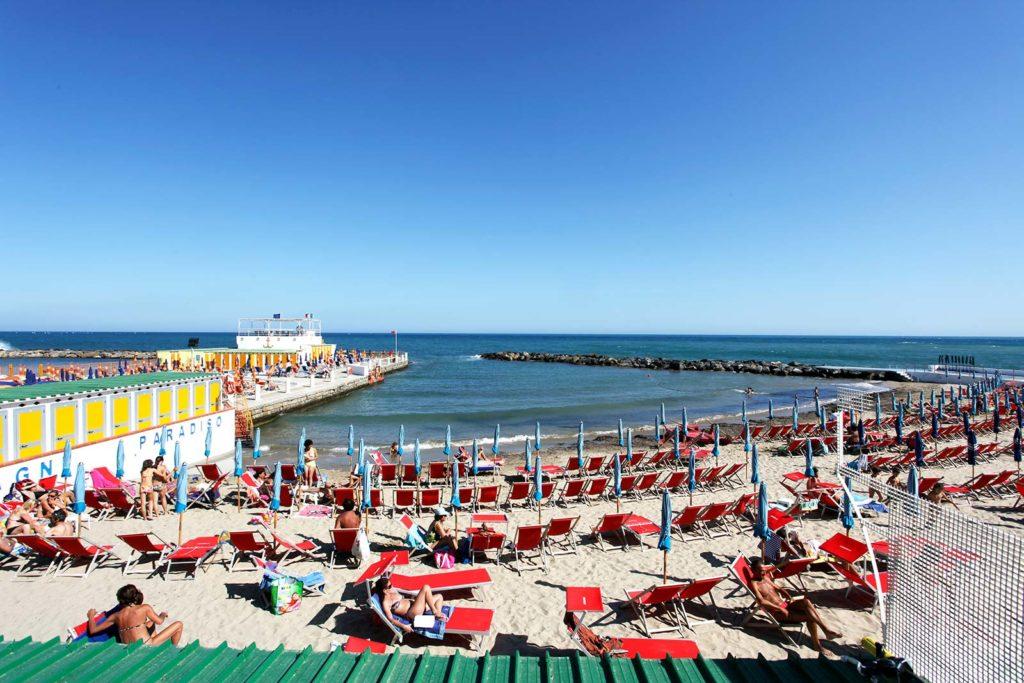 """Praia """"Spiaggia dei porti"""", repleta de cadeiras vermelhas, em São Remo, Itália"""