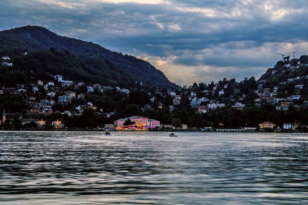 Lago Como, ao anoitecer, com casino iluminado ao fundo.