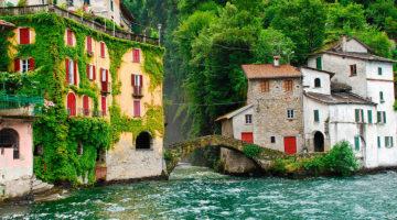 Ponte e casario antigo, junto a zona muito verdejante, no Lago Como